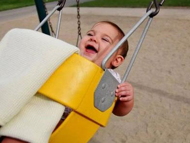 Happy baby on swing at a playground.PNG