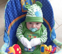 Cute baby boy in green sitting on his chair.PNG